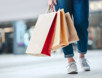 A person wearing sneakers and cuffed jeans carries shopping bags through a mall