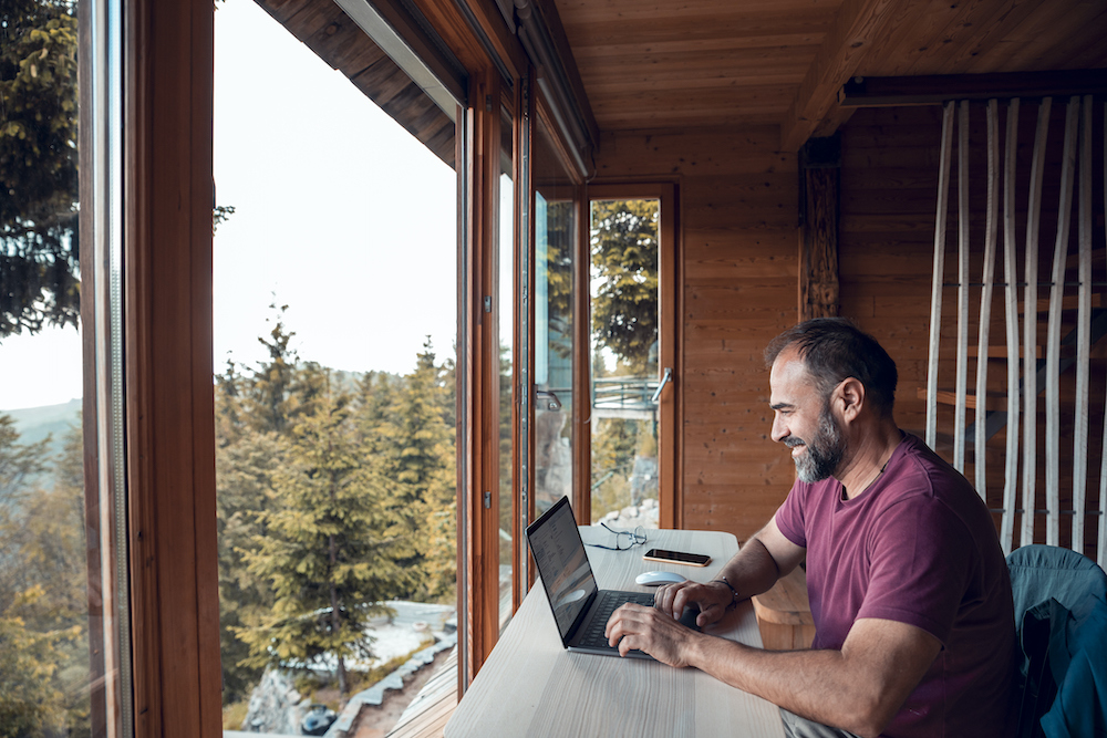man working remotely from mountain cabin